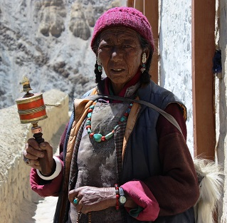 The hardy Ladakhi woman with her face parched in harsh sun. She holds the Prayer handle in her hand.